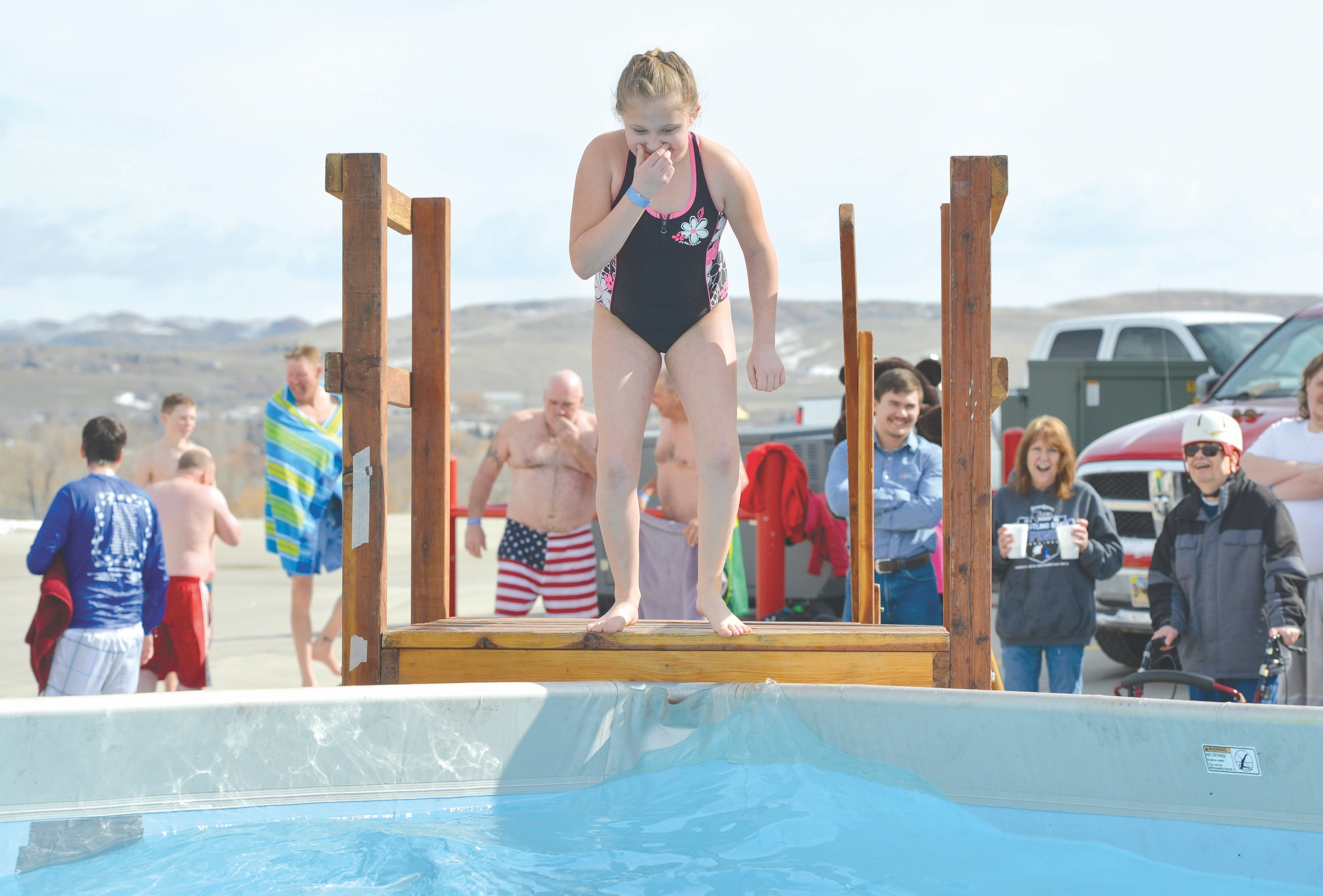 Justin Sheely | The Sheridan Press Nine-year-old Kaylah Pleines plugs her nose before leaping into the water during the annual Jackalope Jump Saturday at Goose Valley Fire Department. Special Olympics athletes, law enforcement agencies and volunteer firefighters jumped in the pool with at temperature of 38 degrees fahrenheit to raise money for the Wyoming Special Olympics.